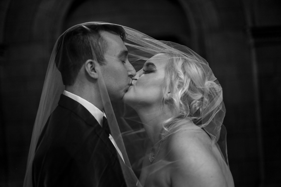 A black and white image of bride and groom kissing under her veil at the Cathedral of Learning