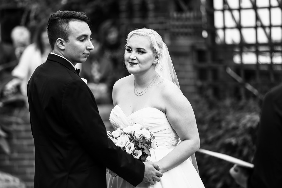a Black and White image of Alexsys looking at Jon on their wedding day at Phipps Conservatory