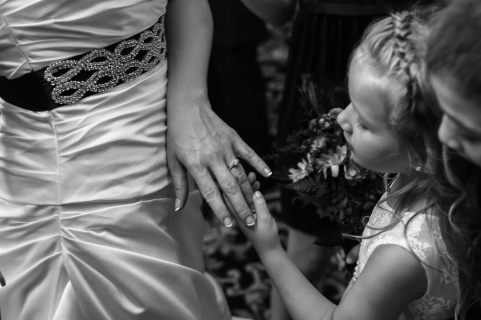 Brides daughter admiring her mothers wedding ring in black and white at Justin and Amandas Warner Theater Wedding