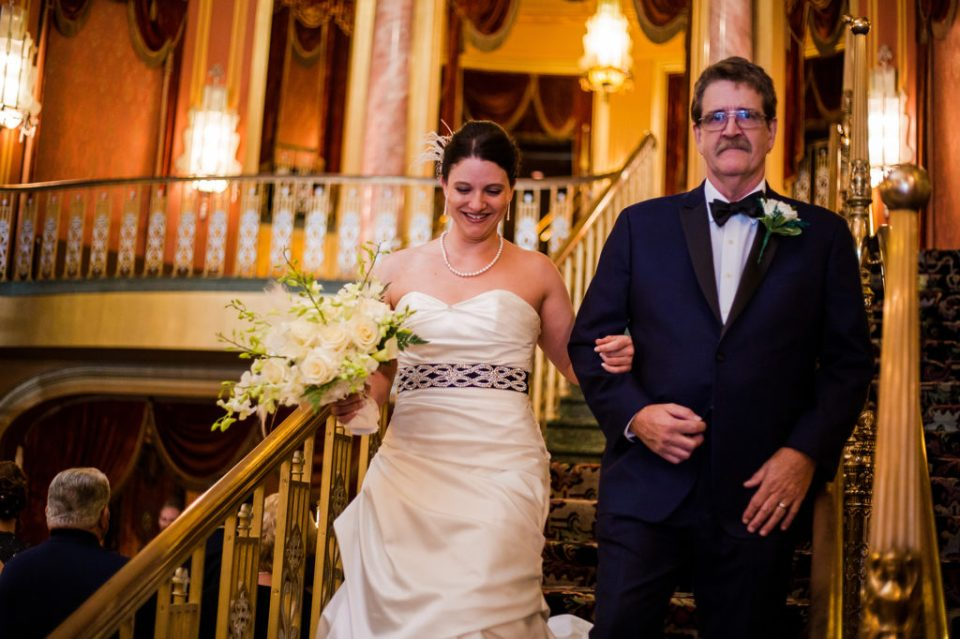 Father of the Bride escorting his daughter down the grand stair case at Amanda and Justins Warner Theater Wedding
