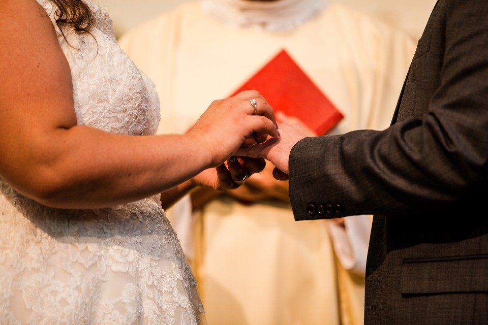 Erie, PA bride and groom exchange rings at Blessed Sacrament Church wedding