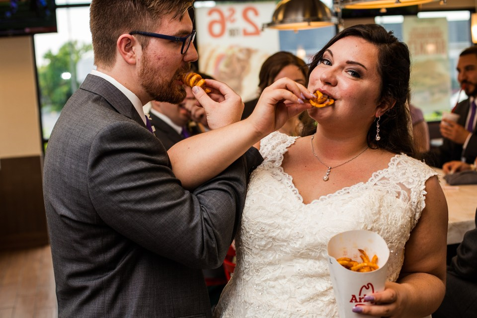 Erie, PA bride and groom eating curly fries together at Arby's restaurant