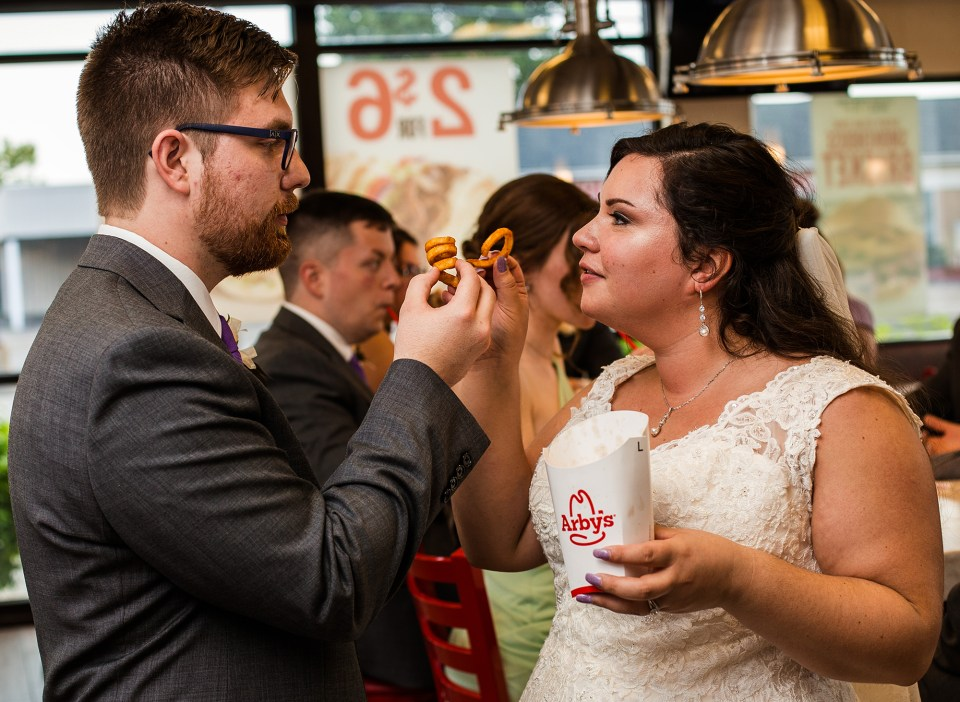 Erie, PA bride and groom toast with curly fries at Arby's restaurant