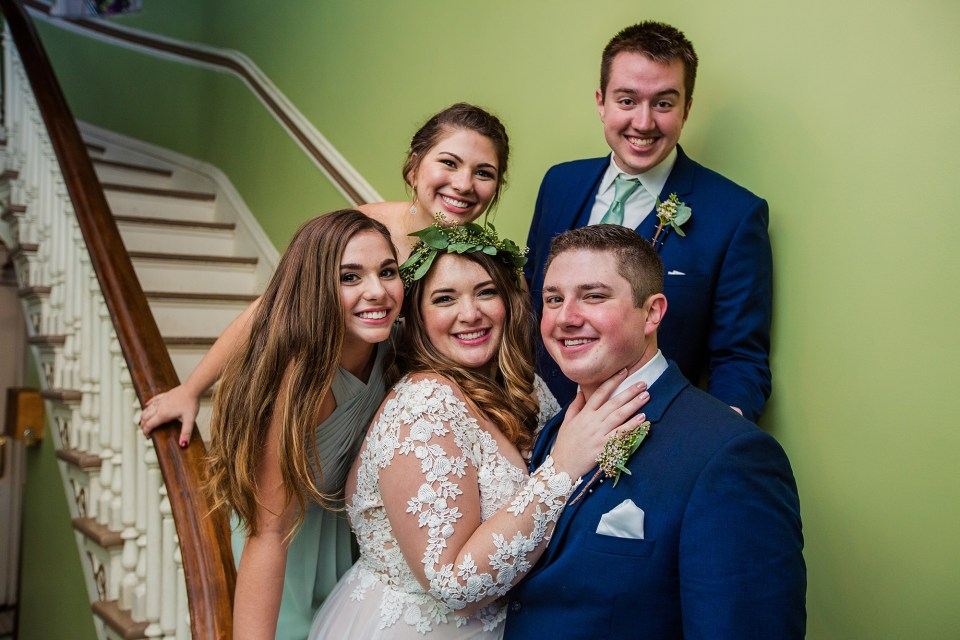 Couple with their bridal party along the staircase at the Waterford Hotel