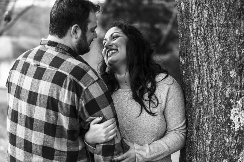 Woman looks loving at fiance during winter engagement photos