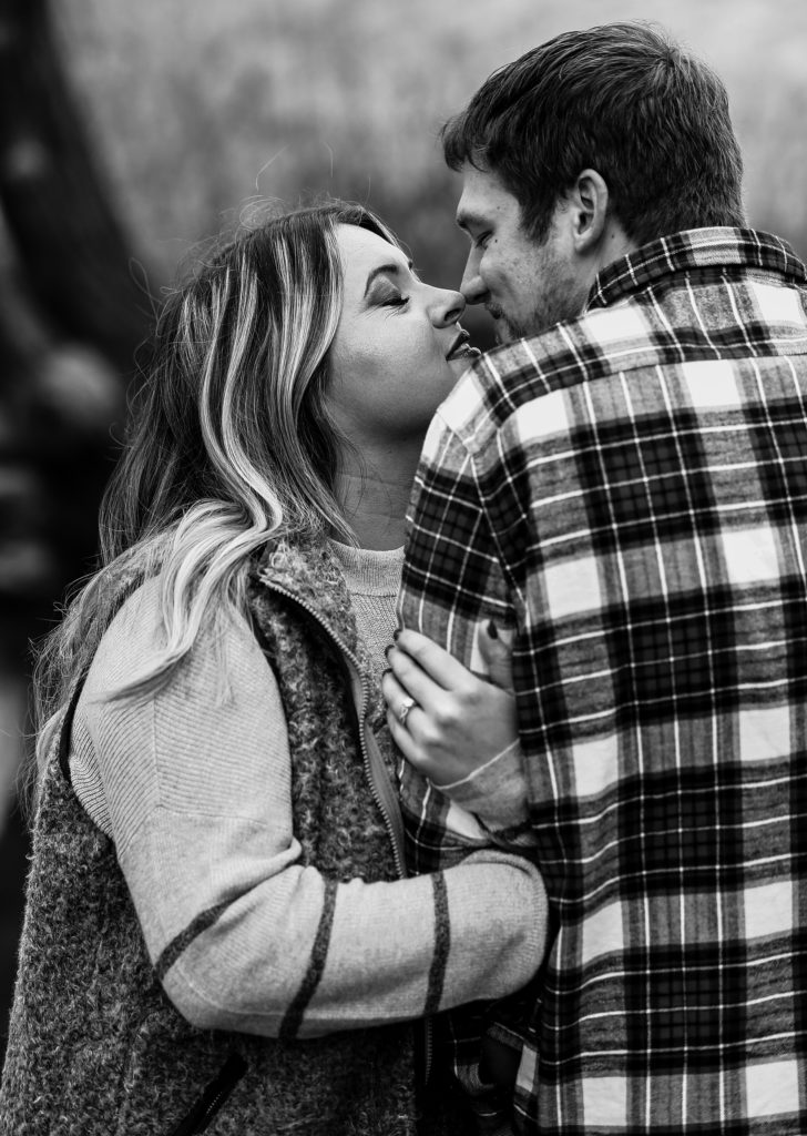 Erie PA couple are about to kiss during fall engagement photos at Frontier Park