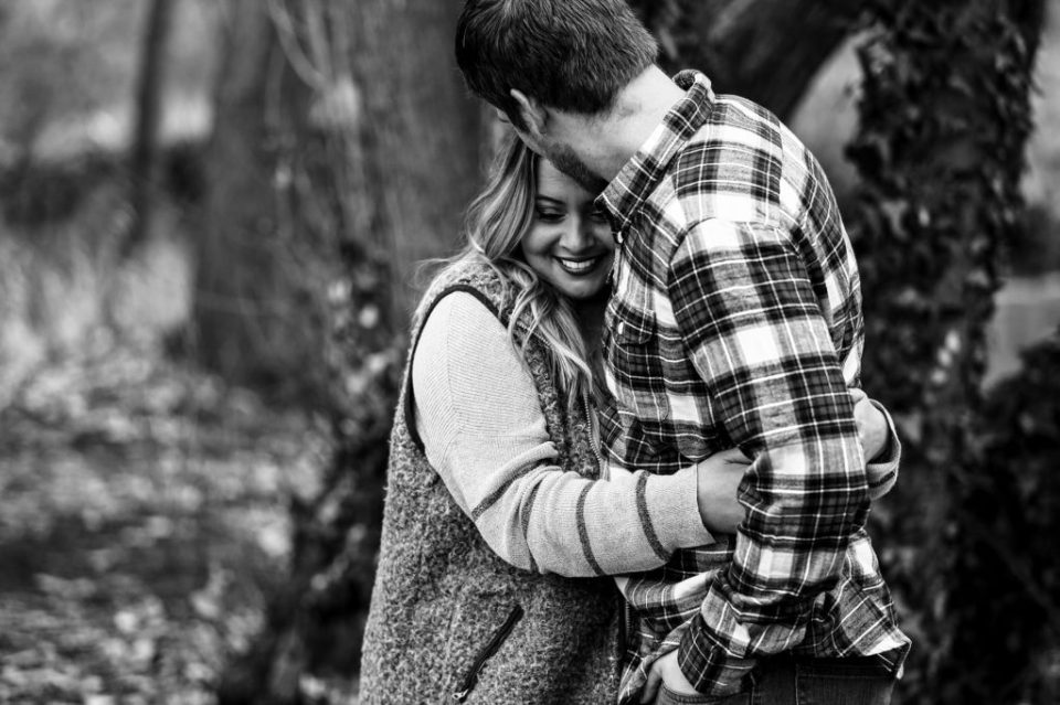 Erie PA woman hugs fiance during fall engagement photos in Frontier PArk