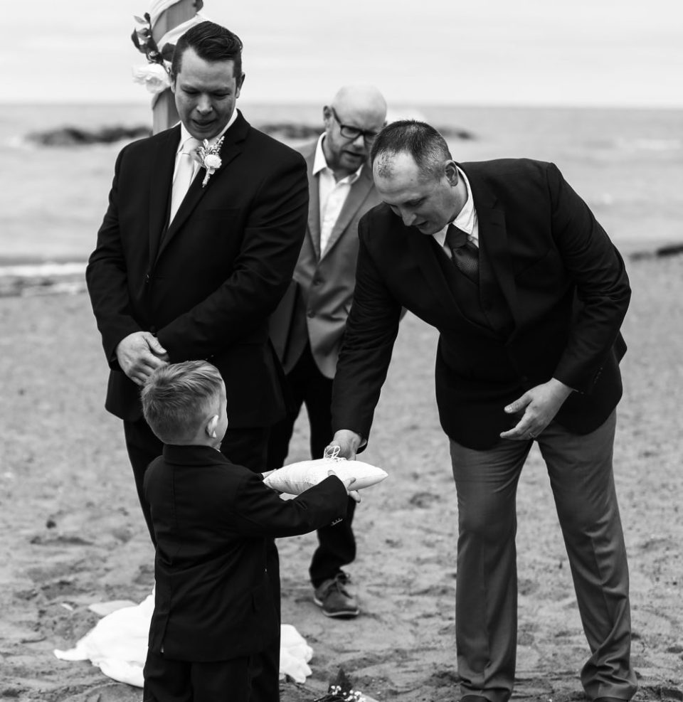 Boy hands rings to best man at Presque Isle beach wedding