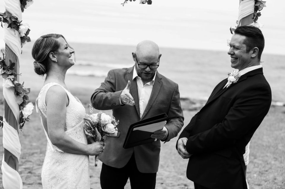 Bride and groom laugh during Presque Isle beach wedding ceremony