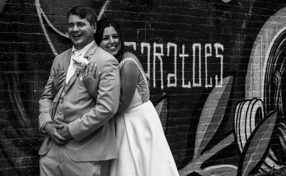 Bride and groom pose together in front of graffiti filled wall in Pittsburgh, PA