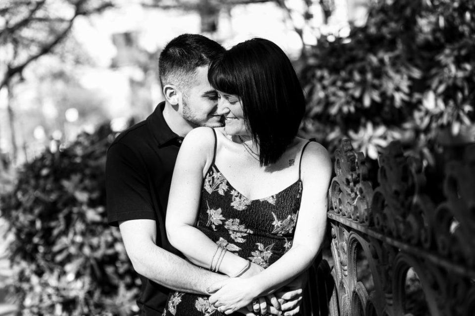 Couple embraces and laughs together next to wrought iron fence in their spring engagement photos