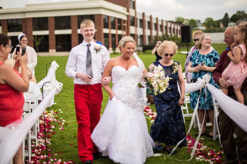 Bride escorted down the aisle during spring vow renewal outside the Sheraton Erie Bayfront Hotel