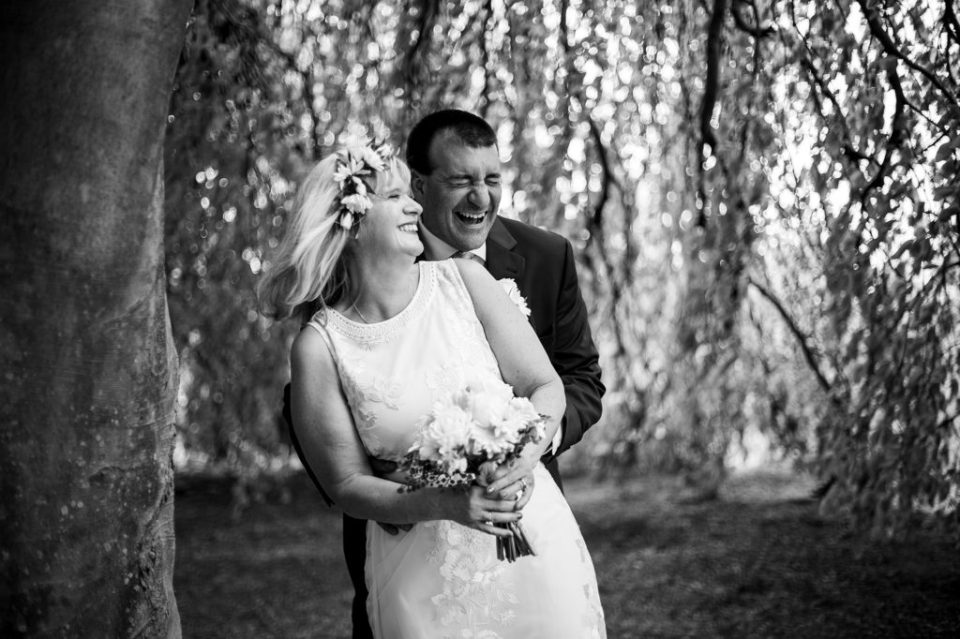 Bride and groom standing under willow tree and laughing during wedding at the Schoolhouseduring