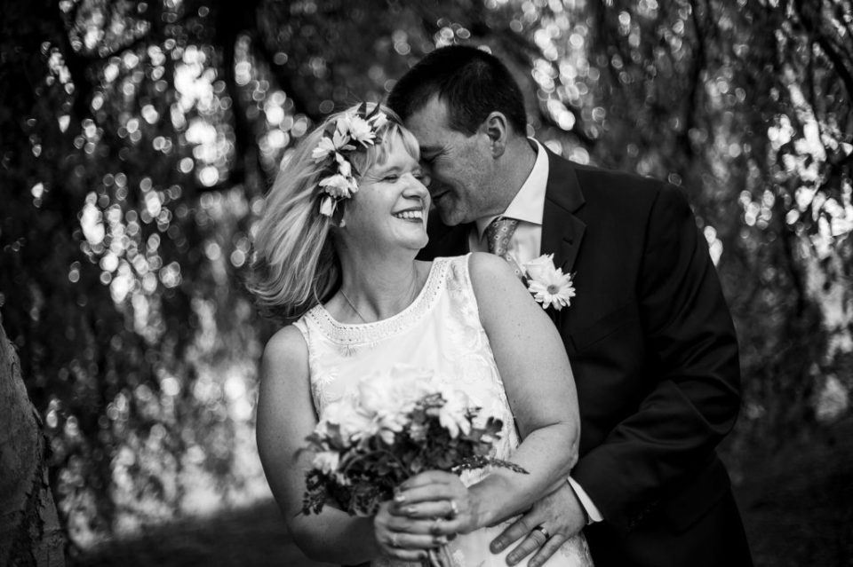 Couple standing under willow tree and smiling at their wedding at the Schoolhouse