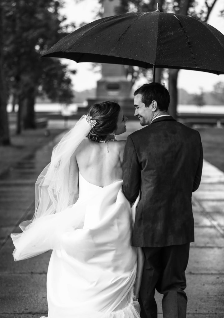 Bride and groom cuddle under an umbrella as they walk toward Perry Monument at Presque Isle State Park