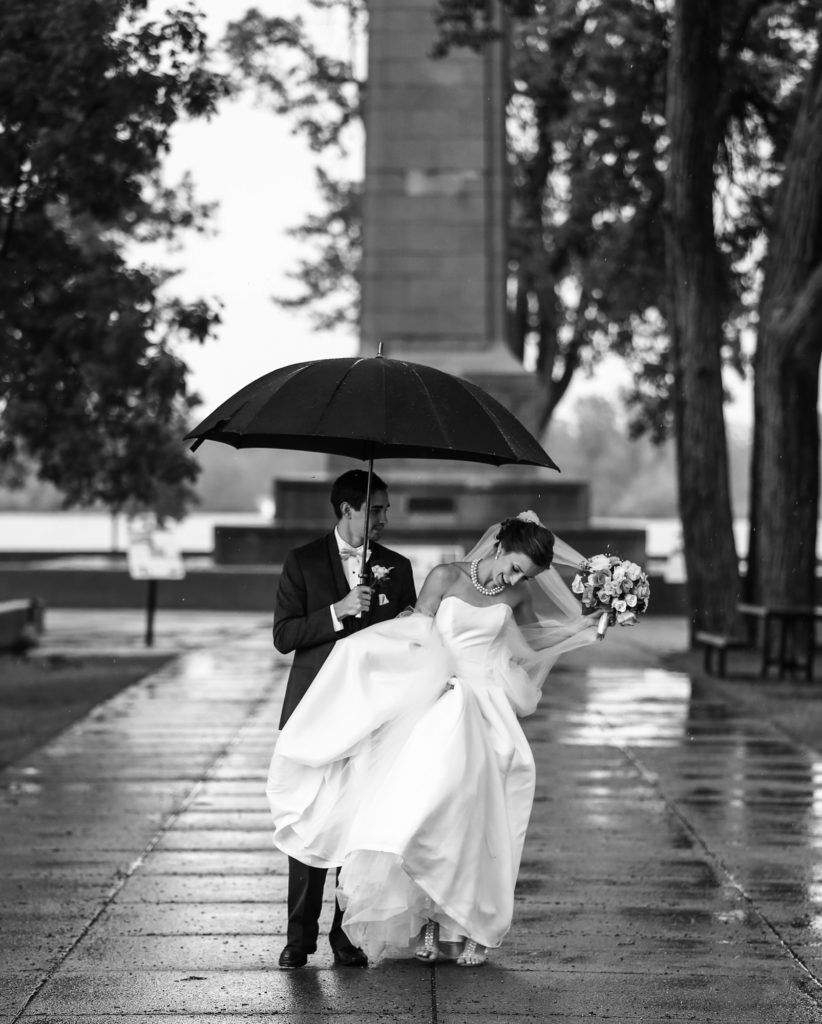 Bride and groom walking under umbrella in front of Perry Monument at Presque Isle State Park