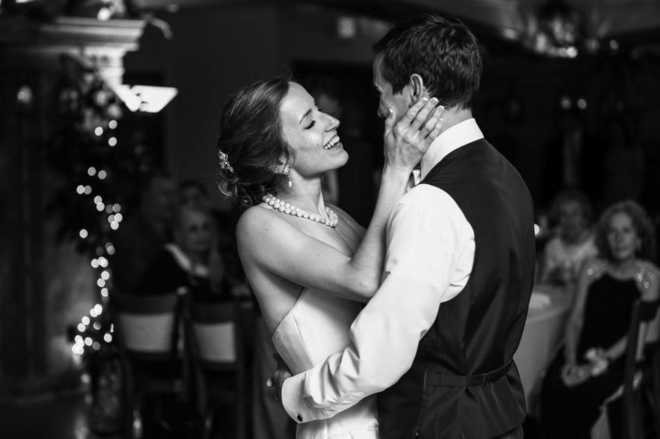 Bride holds groom's face in her hands during first dance at Masonic Temple wedding reception in Erie, PA