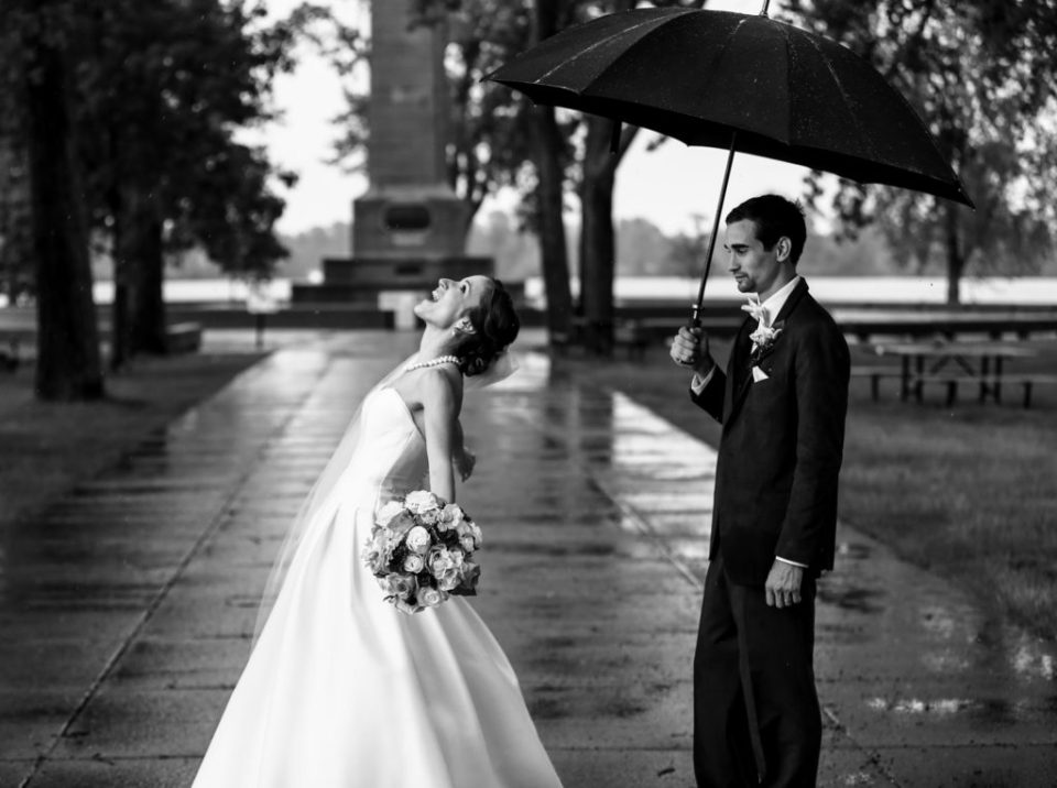 Bride enjoys the rain while groom stands under umbrella at Perry Monument on Presque Isle State Park