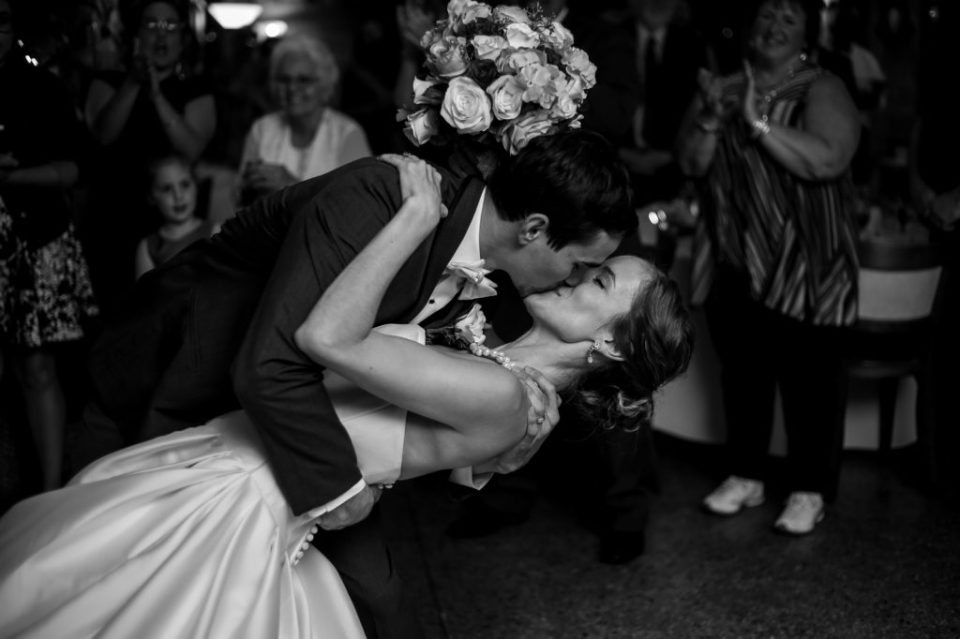 Groom dips and kisses his bride during their Masonic Temple reception in Erie, PA