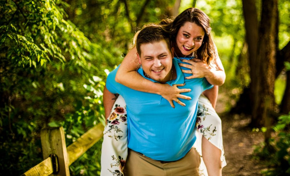 Woman jumps on her fiance's back summer engagement photos at Frontier Park
