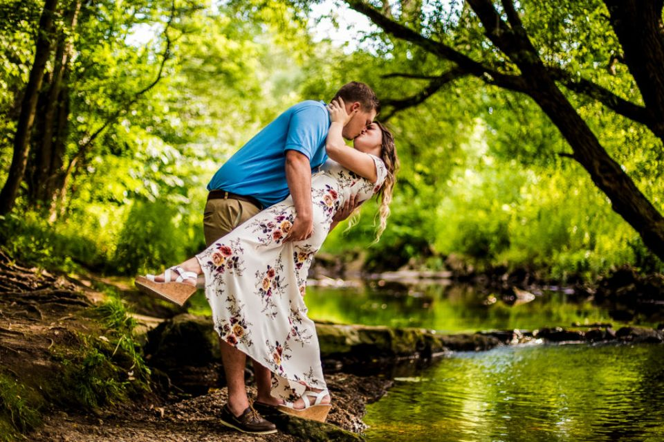 Engaged couple kisses next to Cascade Creek in Erie's Frontier Park