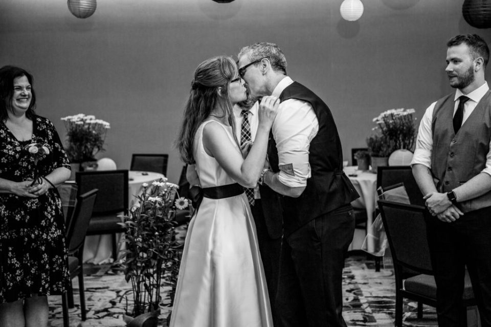 Couple shares fist kiss at their Courtyard Marriott wedding ceremony