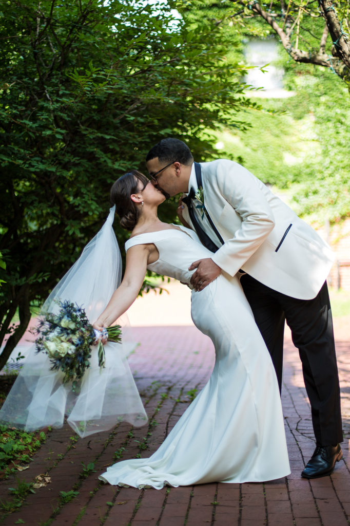 Groom dips his bride while kissing her in Modern Tool Square