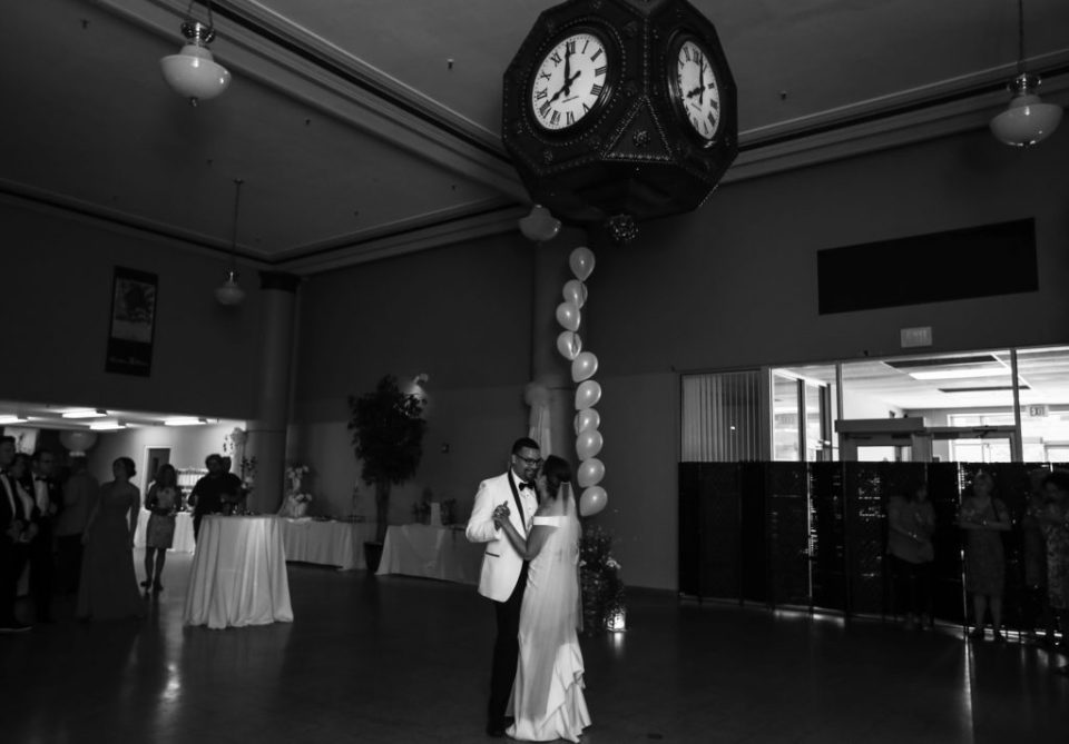 Bride and groom dance under the clock at their Boston Store wedding