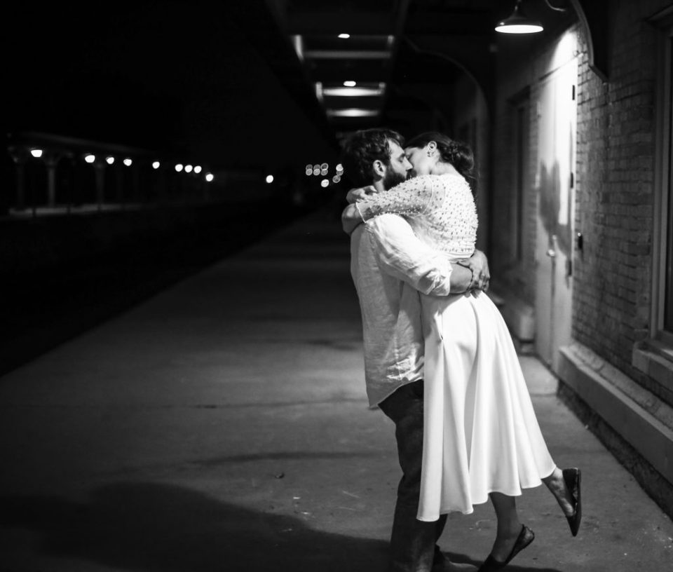 Bride and groom kiss along the tracks at the Brewerie at Union Station