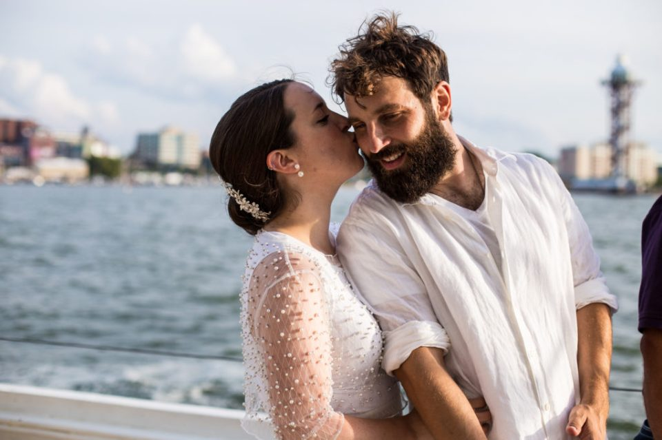 Bride kisses groom on the cheek during tall ship wedding