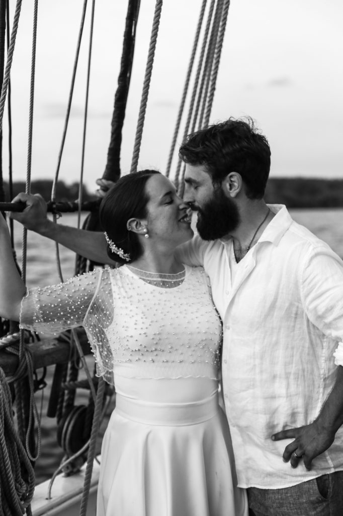 Bride and groom touching noses during their tall ship wedding on the Lettie G. Howard