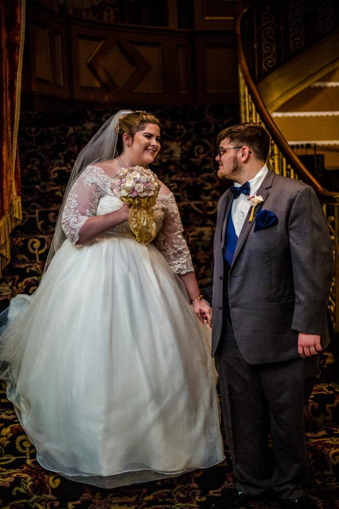 Bride takes groom's hand at summer Warner Theatre wedding
