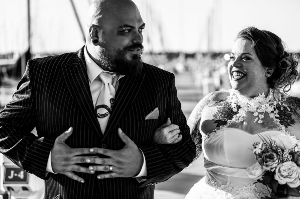 Bride smiles at groom on the docks of the Erie Yacht Club