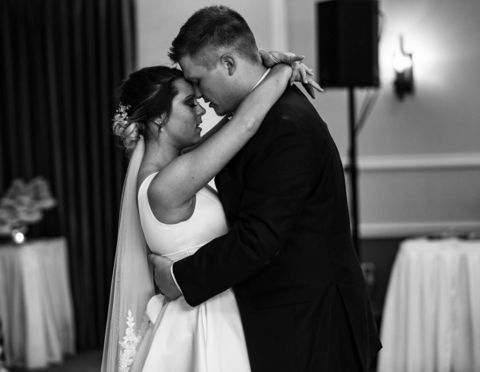 Bride and groom touch foreheads with eyes closed as they dance at their Lawrence Park Golf Club wedding reception