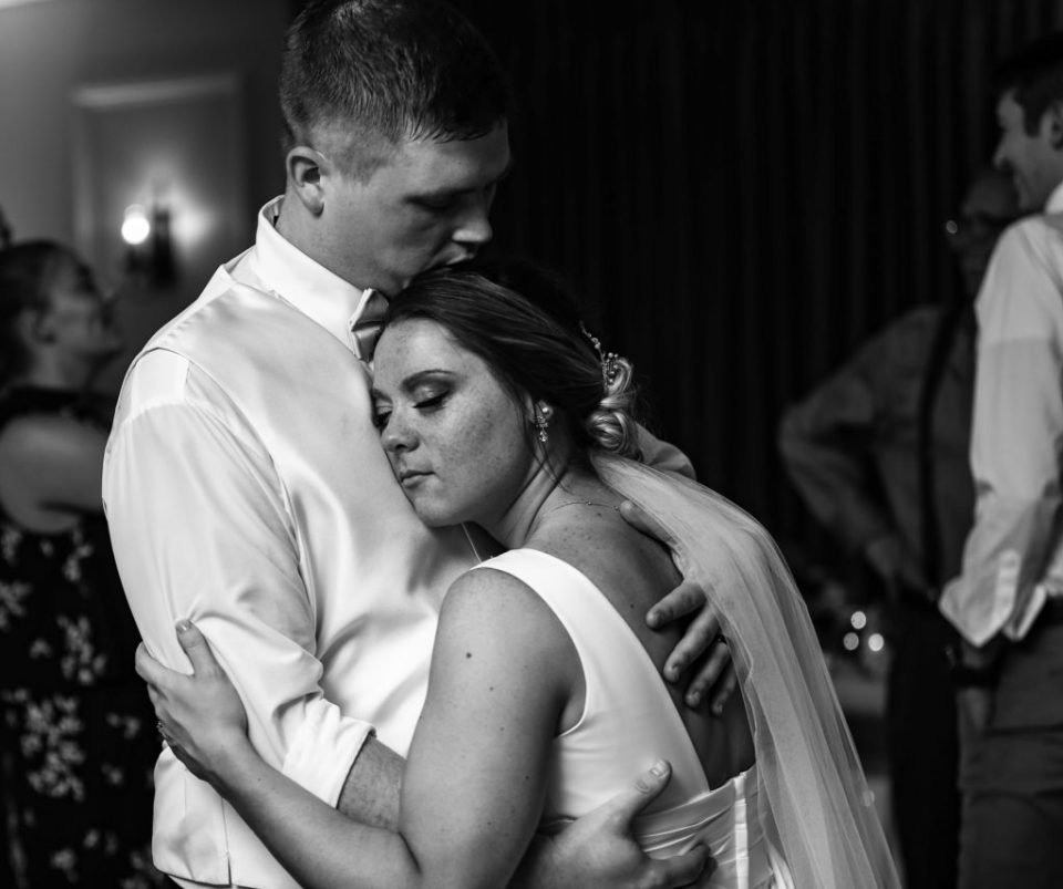 Bride nuzzles groom on the dancefloor of their Lawrence Park Golf Club wedding reception