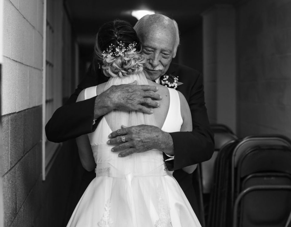 Bride and father embrace during first look photos at Emmanuel Presbyterian Church