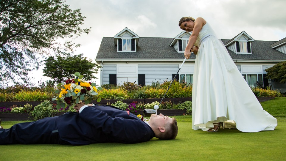 Bride attempts to hit golf ball off a tee in the groom's mouth at Lawrence Park Golf Club