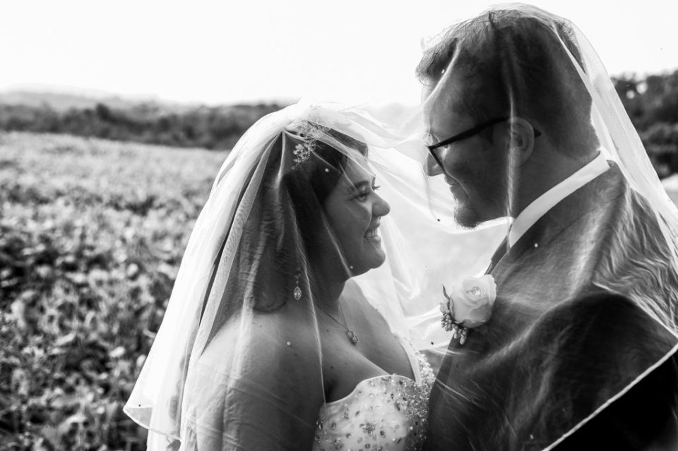 Couple standing under bride's veil in a field during their rustic Connellsville wedding