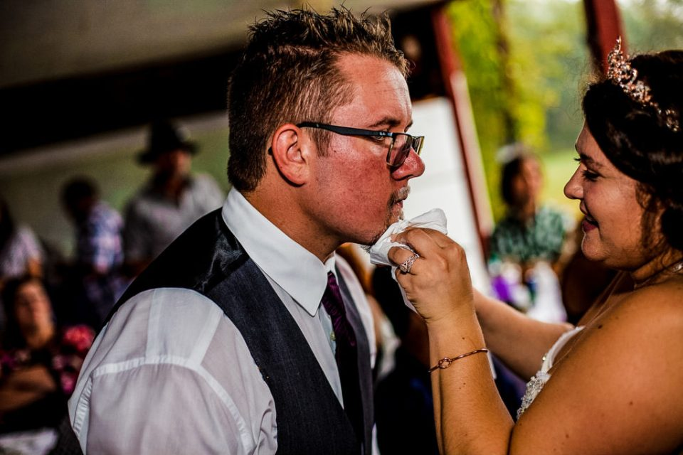 Bride wipes groom's chin during cake cutting at a rustic Connellsville wedding