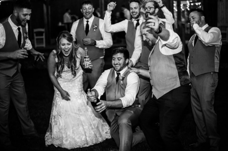 Bridal party laughing as groomsman attempts to open bottle of champagne