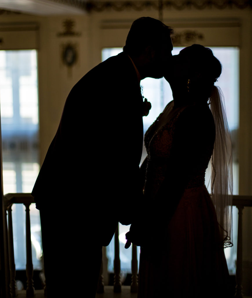 Silhouette of couple kissing on a balcony at the George Washington Hotel