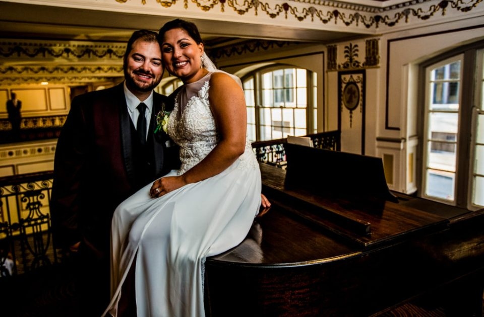Bride and groom pose next to a piano at the George Washington Hotel