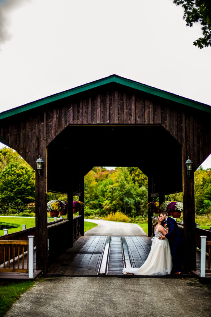 Couple kissing under the covered bridge at Majestic Woods wedding