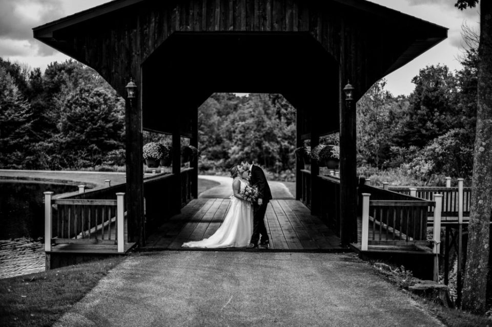 Bride and groom standing under covered bridge at Majestic Woods