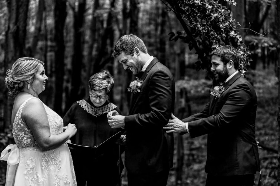 Best man steadies groom as he exchanges rings with bride at Majestic Woods