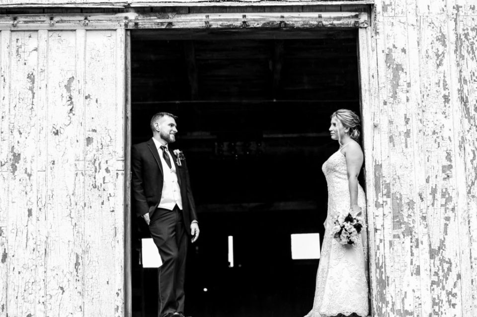 Groom smiles at bride on the second floor of the barn at Barn at Conneaut Creek wedding