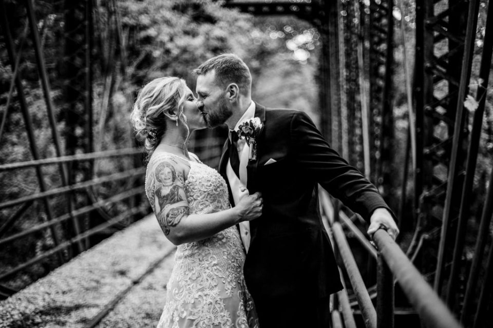 Couple kissing and laughing on the railroad trestle at the Barn at Conneaut Creek