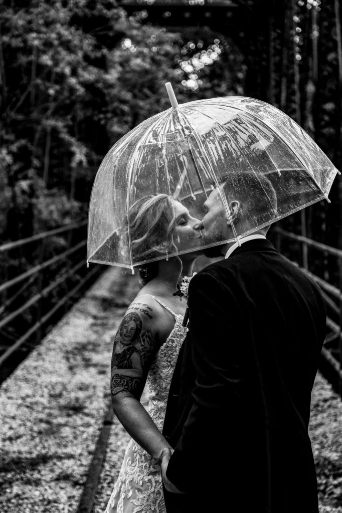 Bride and groom kissing under an umbrella on the trestle at Barn at Conneaut Creek