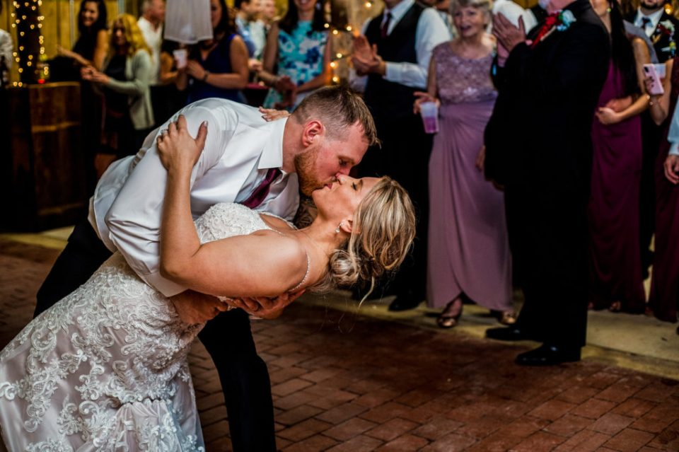 Groom dips and kisses his bride during first dance at Barn at Conneaut Creek wedding