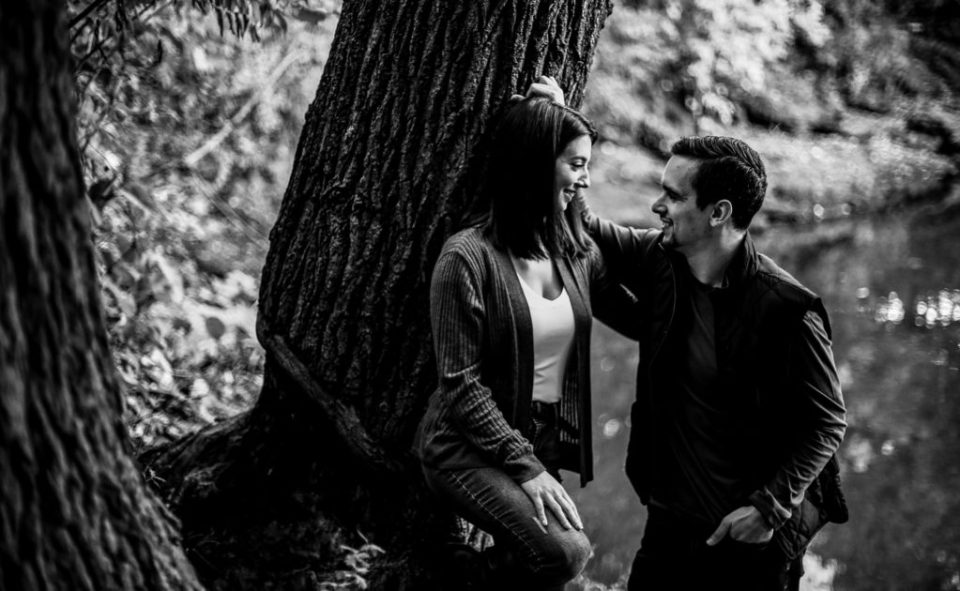 Engaged couple in Erie, PA smile at each other engagement photos at Frontier Park